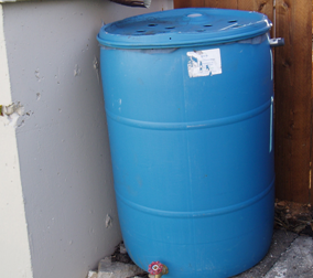 A simple rain barrel with intake from a downspout (top), a drainage spout (bottom), and an overflow spout (side).